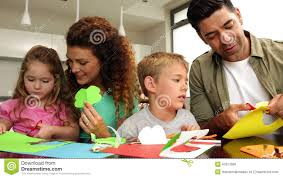 happy parents and children doing arts and crafts at kitchen table