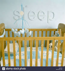 child s cot with sleep letters above in nursery bedroom stock