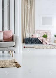 canapé king size rideau beige dans loft multifonctionnel avec canapé gris et couvre