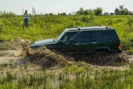mud jeep cherokee off road vehicle brand jeep cherokee overcomes a pit of mud stock