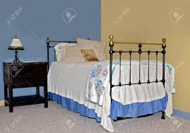 twin iron and brass bed on walls painted contrasting colors with