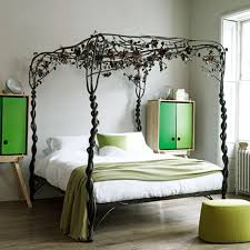 Green Laminate Flooring Black Metal Canopy Bed With Green Blanket And Pillows Combined By