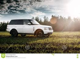 green range rover car land rover range rover stand on green field near forest at