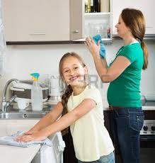 maman cuisine la fille mignonne aider maman adulte dépoussiérage dans la
