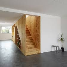timber stairs storage wall with integrated shelving and kitchen