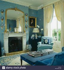 large gilt mirror above marble fireplace in blue sitting room with