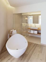 white glossy porcelain bathtub in brown marble bathroom wall panel