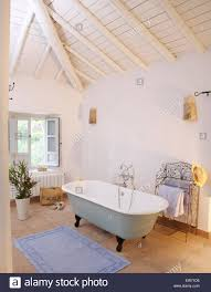 roll top bath in white spanish bathroom with white painted beamed