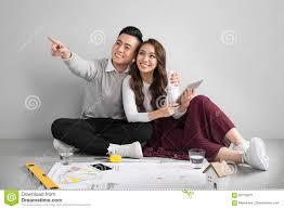 young asian couple sitting on flor planning new home desig