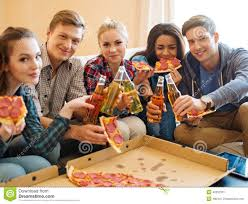 multi ethnic friends with pizza and bottles of drink stock photo