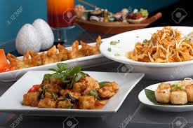 a big assortment of thai foods and appetizers presented