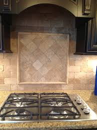 tumbled stone 3x6 backsplash with cooktop accent on diagonal with