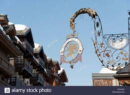 ornate metal signs hanging on building walls in courchevel 1850