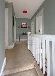 grey upstairs hallway with white railing and beige carpet stock
