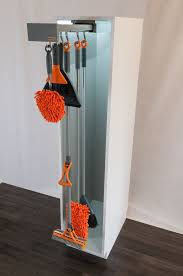 storage cabinets for mops and brooms glideware stores your mops brooms and other cleaning items by