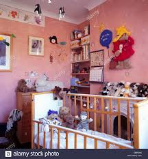 paddington nursery soft toys in baby s cot in pink nursery bedroom with large felt