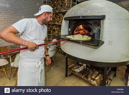 young kitchen chef check pizza in traditional wood fired oven