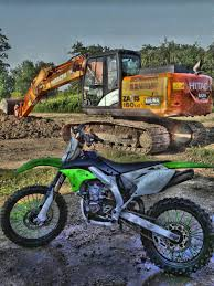 motocross dirt bike green black and gray motocross dirt bike near hitachi power truck