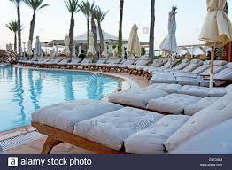 row of empty sun loungers around a resort swimming pool stock