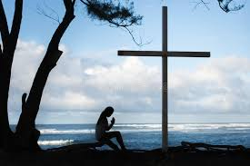 praying to god in front of a cross with a beautiful blue