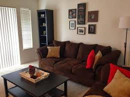 living room with red accents tan living room with red accents white rug white wall color white