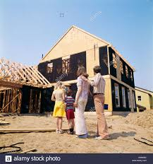 1970s family of four looking at new home under construction man