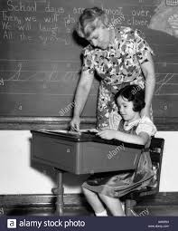 Student At Desk by 1930s Female Teacher In Front Of Blackboard Helping Girl Student