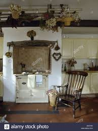 antique windsor chair in front of white aga oven in traditional