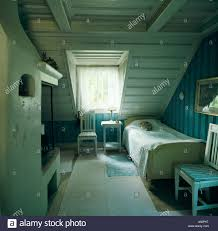 rug on floor beside single bed in white attic bedroom in