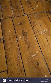 close up of old scratched and worn pinewood floor boards stock