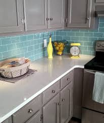 backsplashes white subway tile going up the wall in the kitchen