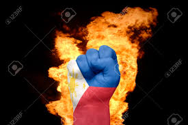 Flag On Fire Fist With The National Flag Of Philippines Near The Fire On A