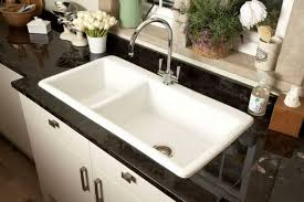 white sink black countertop two bowl undermount porcelain sink with chrome faucet in the kitchen