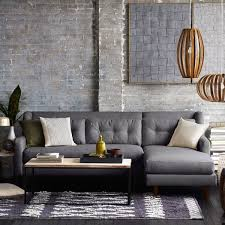 west elm arc l l shaped mid century sofa in a living room with grey brick walls