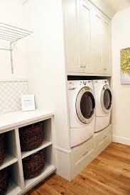 white arabesque tile backsplash over laundry room shelving unit