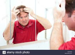 middle aged man checking for thinning hair in the mirror stock