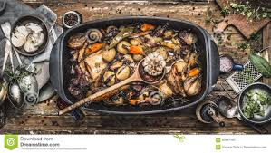 country stew in vintage casserole with cooking spoon and roasted