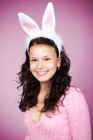 halloween pink background woman in pink sweater wearing bunny headband smiling against pink
