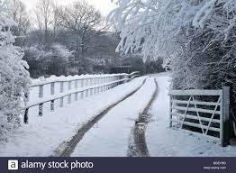 winter entrance drive to country property stock photo