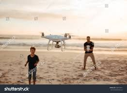 father son operating drone by remote stock photo 658472641
