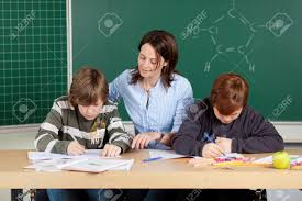 Picture Of Student Sitting At Desk Portrait Of Teacher With Elementary Students Sitting At Desk