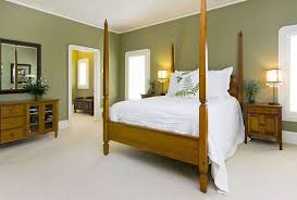 bedroom with sage green warm paint colors and wooden furniture