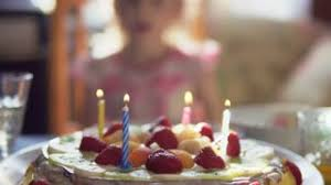 little blows candles on birthday cake photo flashes stock