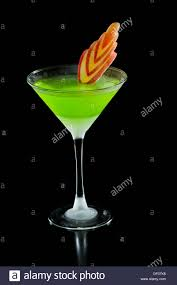 neon green martini served on a black background garnished with