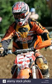motocross bikes for sale ni a motocross bike rider riding down a hill on a gravel track stock