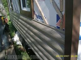 faux log siding going up on a home shows just how simple the
