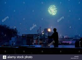 lanterns fireworks boy standing on rooftop silhouetted against fireworks and lanterns