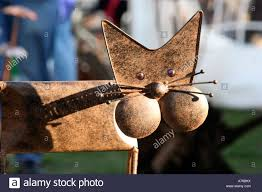 a cat statue on a stall selling outdoor garden ornaments at the