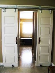 white wooden interior barn doors with colonial style carving of