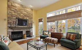 open plan family room with sandstone fireplace and yellow walls